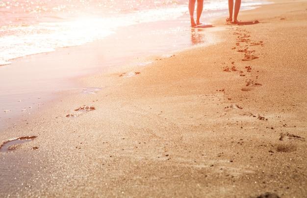 Pegadas de praia, onda e mulheres ao pôr do sol tempo com sol flare