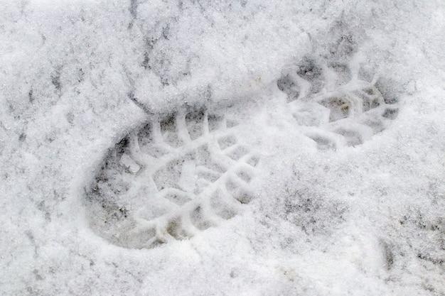 Pegadas de sapatos na neve molhada, fundo de inverno