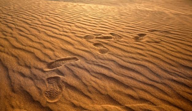 Pegadas de solado na areia do deserto, passos humanos em lugar de natureza selvagem