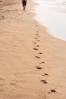 Pegadas de um homem andando na praia. conceito de viagem