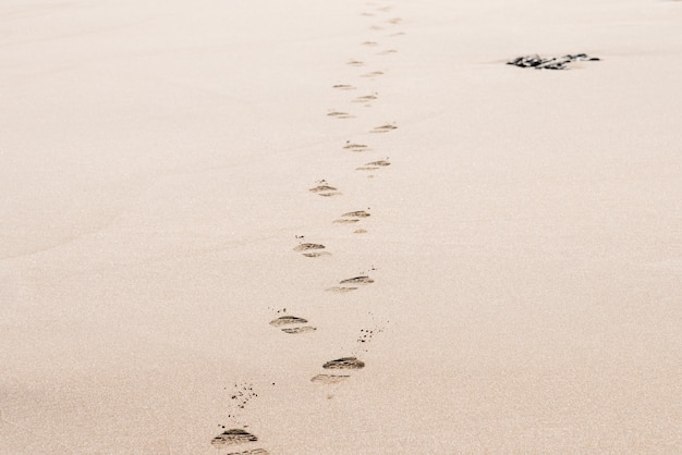 Pegadas de um homem na areia do deserto em um dia ensolarado