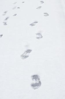 Pegadas de um homem na neve branca no inverno, fundo do inverno