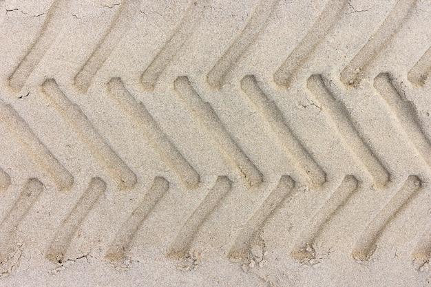 Pegadas do passo do pneu de um trator na praia da areia, textura da areia para o fundo.
