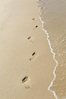 Pegadas e ondas na areia
