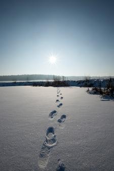 Pegadas em montes de neve após caminhada, congelamento e queda de neve no inverno