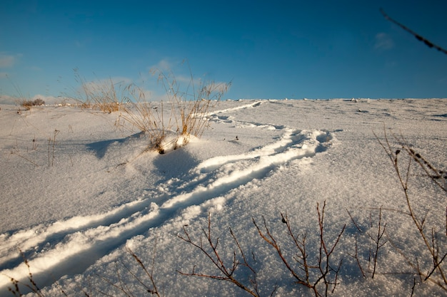 Pegadas em montes de neve depois de caminhar pela neve de uma pessoa, o inverno na natureza