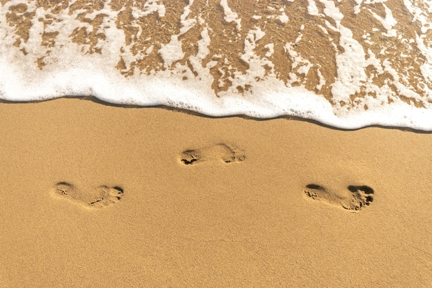 Pegadas humanas na praia de areia