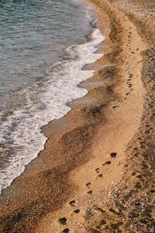 Pegadas humanas se estendem ao longo da praia