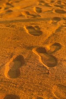 Pegadas na areia amarela dourada junto ao mar tranquilo natural