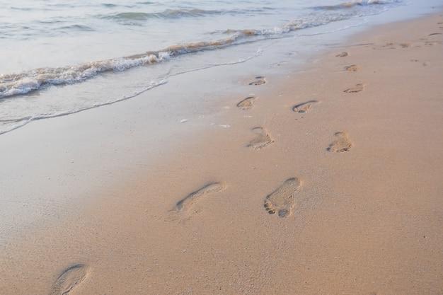 Pegadas na areia ao pôr do sol. praia tropical com ondas do mar