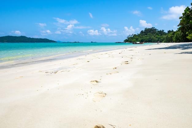 Pegadas na areia branca e mar cristalino na ilha lipe