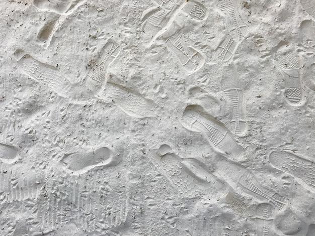 Pegadas na areia branca na praia