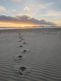 Pegadas na areia cinza