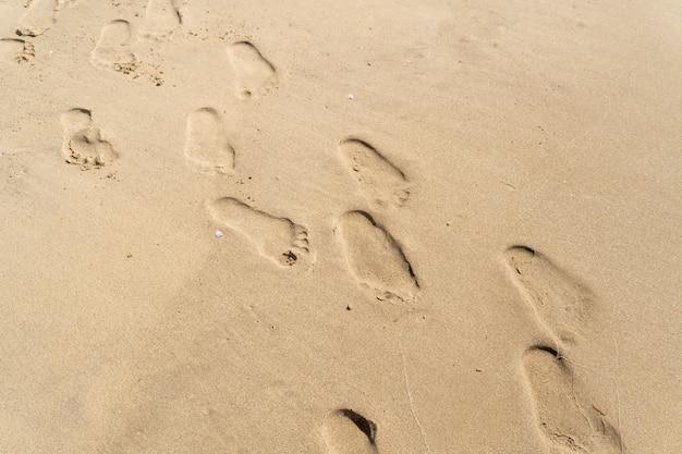 Pegadas na areia da praia, verão.