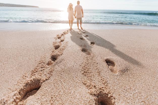 Pegadas na areia de um homem e uma mulher ao pôr do sol