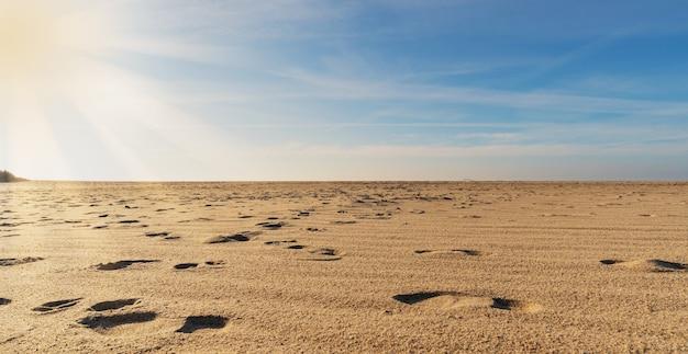 Pegadas na areia iluminadas pelos raios do sol e pelo azul do céu