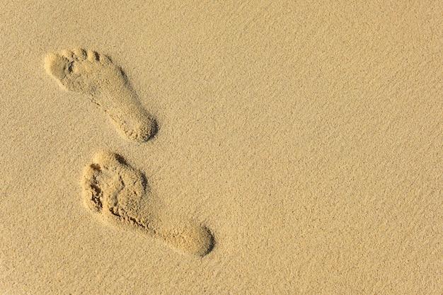 Pegadas na areia molhada do mar na praia