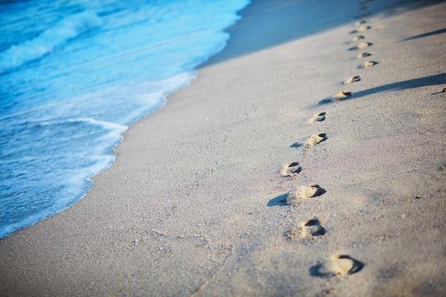 Pegadas na areia perto do mar