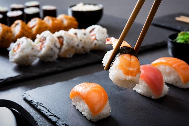Pegando um pedaço de sushi com pauzinhos