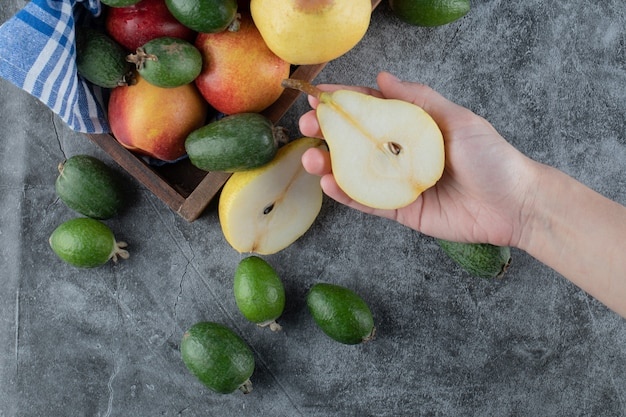 Pegando uma pêra meio cortada da bandeja de mix de frutas