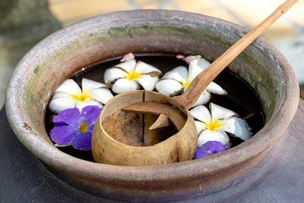 Pegue a casca do coco e uma jarra de barro cheia de água e flores. tailândia. fechar-se
