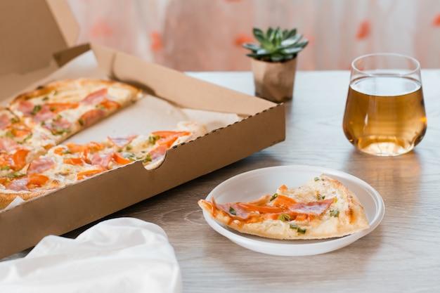 Pegue a comida. uma fatia de pizza em um prato plástico descartável, cerveja e uma caixa de pizza na mesa da cozinha.