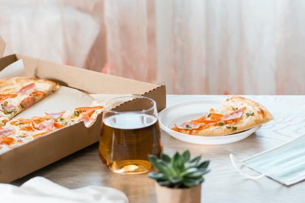 Pegue a comida. uma fatia de pizza em um prato plástico descartável e uma caixa de pizza na mesa da cozinha.