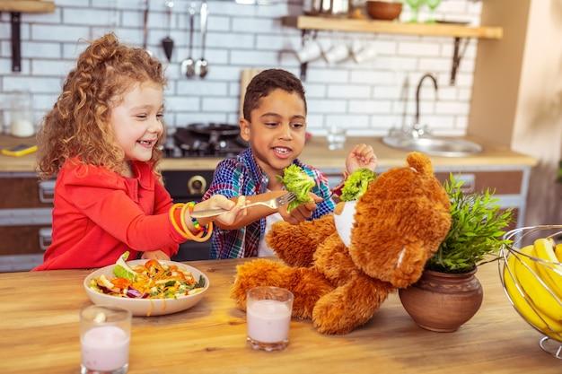 Pegue. criança morena alegre sentada perto de seu amigo dando brócolis para seu urso de brinquedo