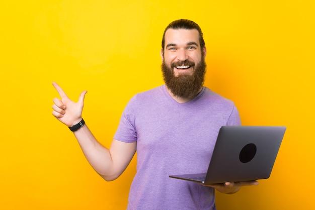 Pegue esta oferta. homem barbudo está segurando um laptop enquanto aponta para cima.