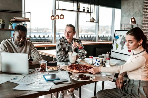 Pegue. homem loiro sério sentado perto de um colega internacional enquanto comia comida asiática
