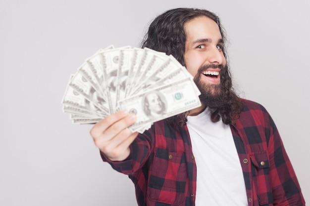 Pegue! jovem empresário kidness feliz em camisa quadriculada vermelha e cabelo longo cacheado em pé, segurando muitos dólares, olhando para a câmera com a boca aberta. foto em estúdio interno, isolada em fundo cinza