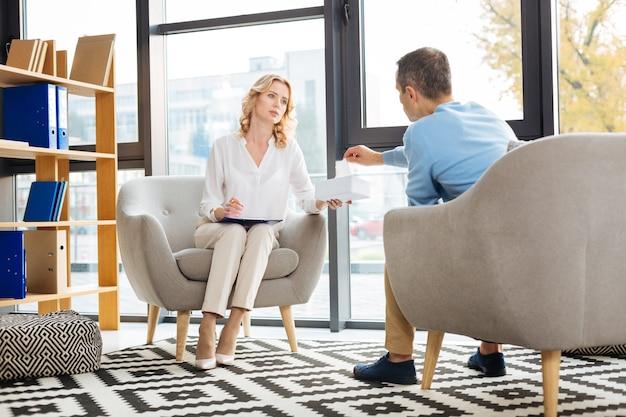 Pegue. mulher simpática agradável e simpática segurando uma caixa de lenço de papel e oferecendo ao paciente durante uma sessão psicológica
