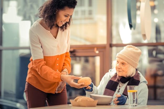 Pegue. mulher simpática e encantada oferecendo um pãozinho enquanto fica perto da sem-teto