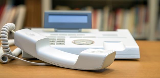 Pegue o telefone na mesa do escritório.