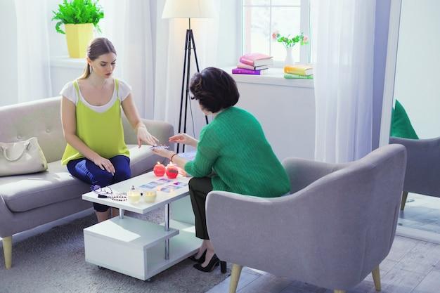 Pegue um cartão. boa cartomante profissional segurando um baralho de cartas de tarô durante uma sessão com seu cliente