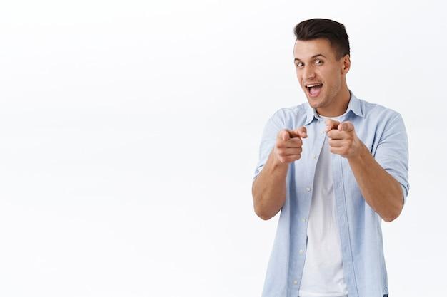 Peguei vocês. retrato de jovem bonito carismático apontando dedos e sorrindo feliz, escolhendo uma pessoa, convidando você para se juntar ao time, se candidatar a um emprego, parabenizar ou elogiar boa escolha