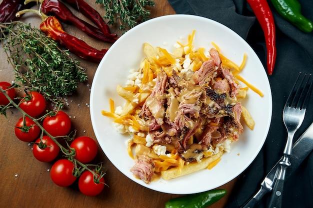 Peito de carne fumador com molho de amendoim e um prato de batatas fritas em uma tigela branca sobre uma mesa de madeira. carne assada. churrasco