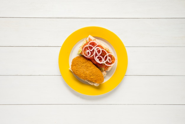 Peito de frango à milanesa e sanduíche de legumes frescos na mesa de madeira