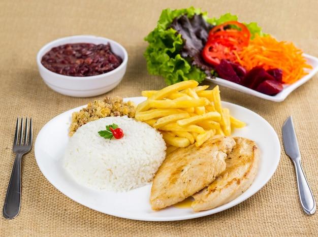 Peito de frango, arroz, feijão, batata e migalhas com acompanhamentos