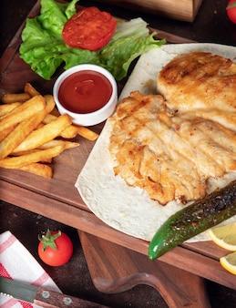 Peito de frango assado com batatas fritas em panela com legumes e ketchup na placa de madeira