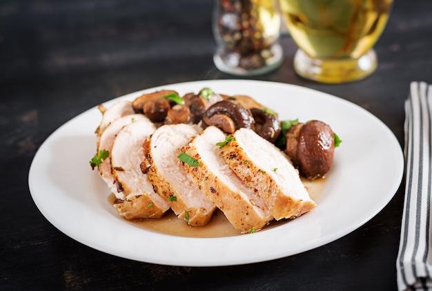 Peito de frango assado com cogumelos em molho balsâmico em cima da mesa.
