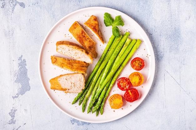Peito de frango assado com espargos e tomates, vista superior.