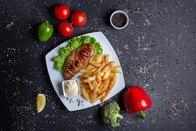 Peito de frango assado grelhado, batatas fritas com molho, em preto com tomates vermelhos, pimentão verde vermelho e brócolis
