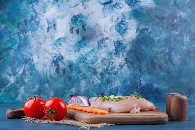 Peito de frango com cenouras fatiadas em uma tábua ao lado da cebola fatiada na superfície azul