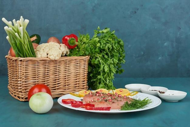 Peito de frango com especiarias em um prato branco com legumes ao redor.