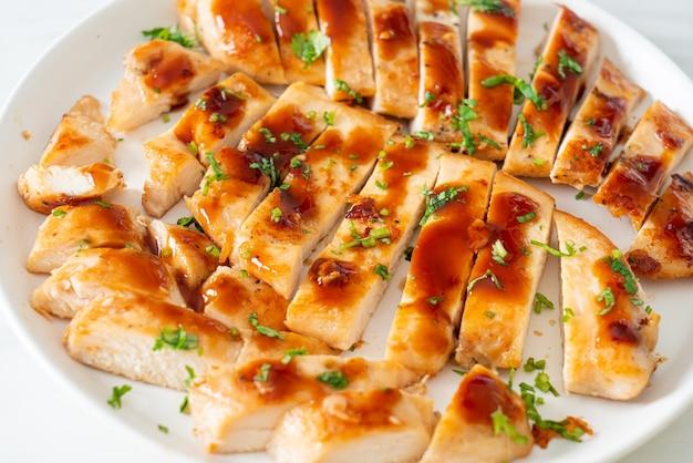 Peito de frango com mel grelhado fatiado em prato branco