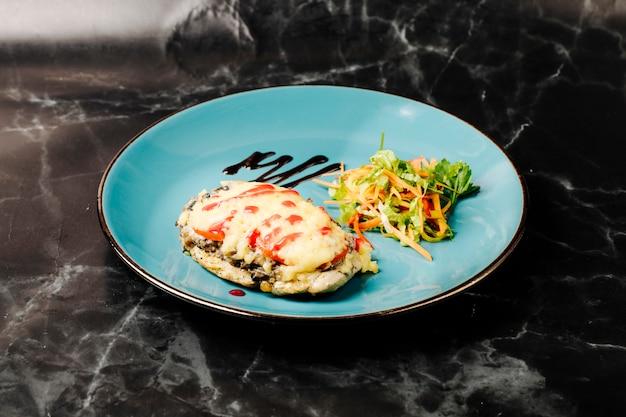 Peito de frango com molho cremoso derretido e molho vermelho na parte superior e salada de legumes em chapa verde.