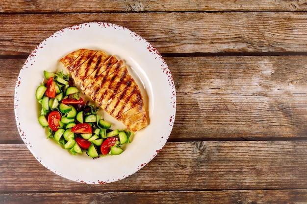 Peito de frango com salada de legumes com pepino e tomate