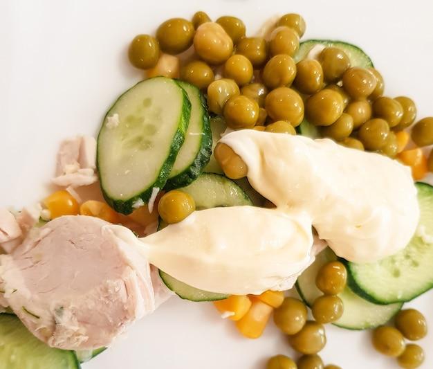 Peito de frango cozido com ervilhas verdes cozidas, pepino e molho em um prato branco. nutrição saudável e equilibrada, o conceito de dieta