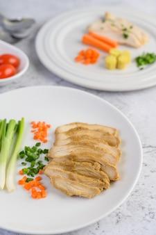 Peito de frango cozido no vapor em um prato branco com cebolinha e cenoura picada